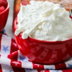 A red bowl with fluffy vanilla frosting ready to frost a cake.