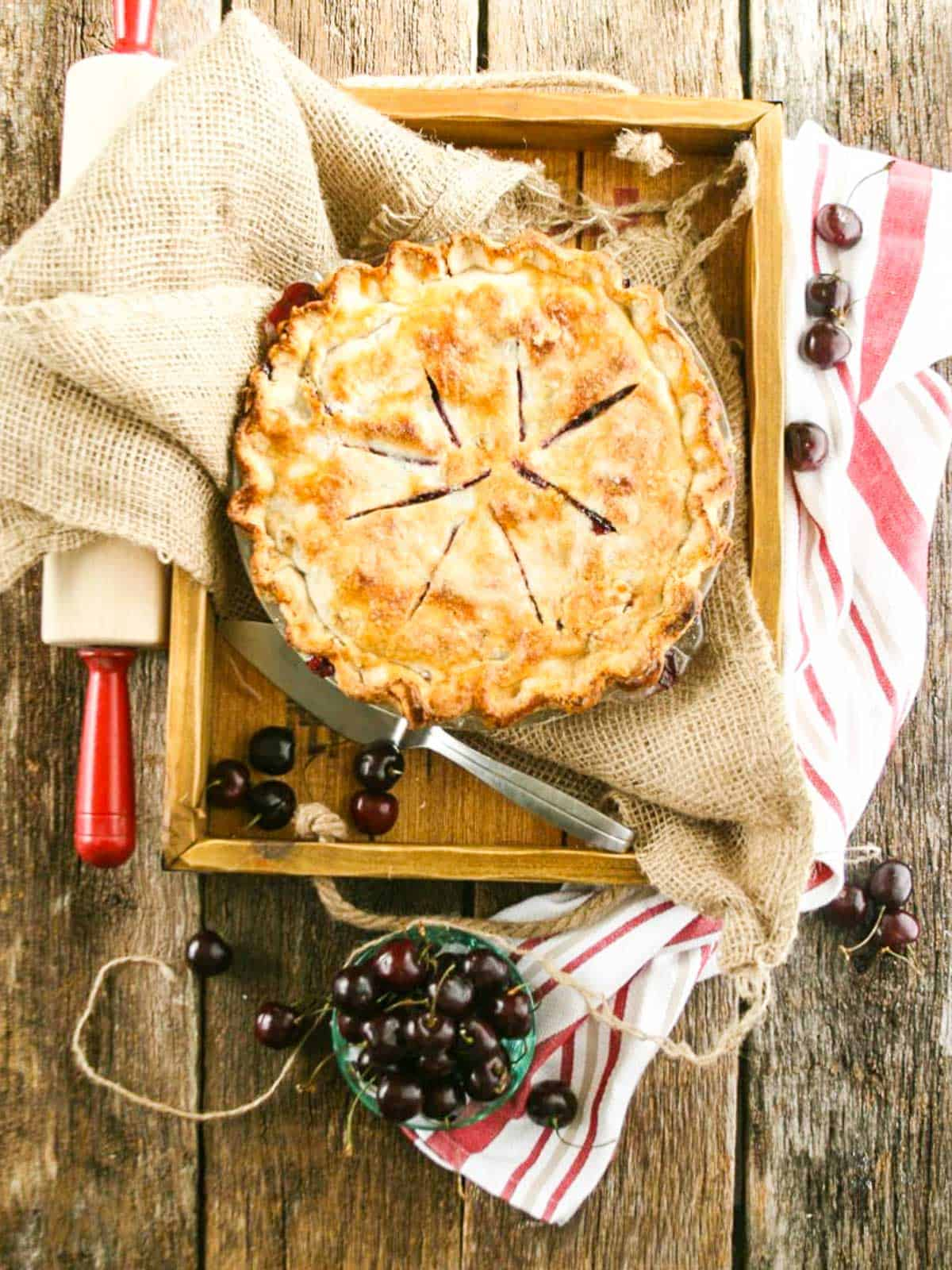 A large cherry pie with rolling pin and bowl of cherries ready to cut a slice.