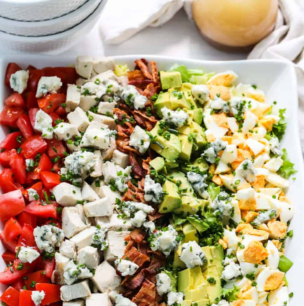 A white square plate filled with colorful Cobb Salad made with chicken, eggs, avocados, tomatoes, and bacon.