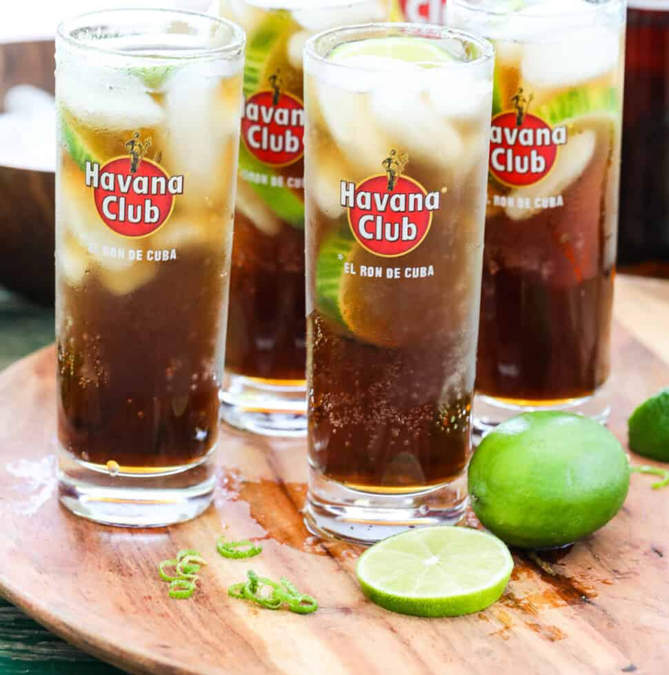 Four tall Havana Club glasses with Cuba Libre cocktails garnished with lime on a wood tray.