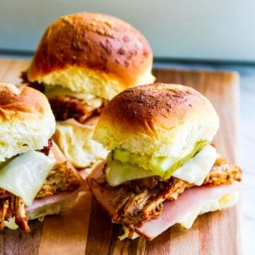 Three pulled pork sandwiches on Hawaiian buns with pickles, cheese and ham on a cutting board.