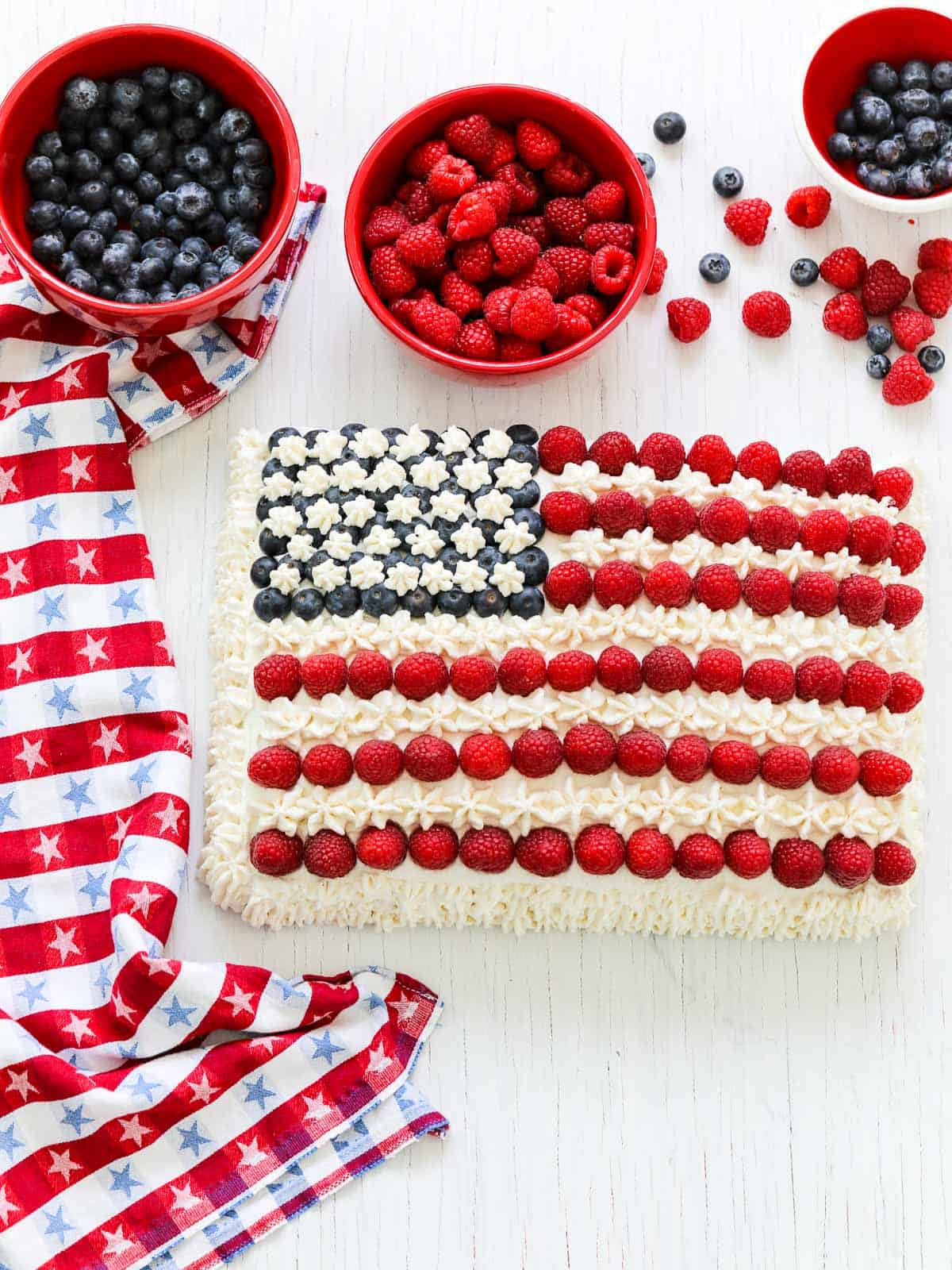 An American flag cake decorated with blueberries, raspberries, and white frosting with a patriotic star towel.