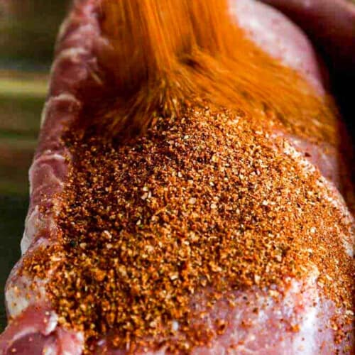 A large pork loin roast with a lot of dry rub seasoning pouring over the top.