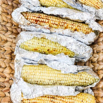 A larger serving basket with Grilled Corn unwrapped in foil laying in the basket before eating.