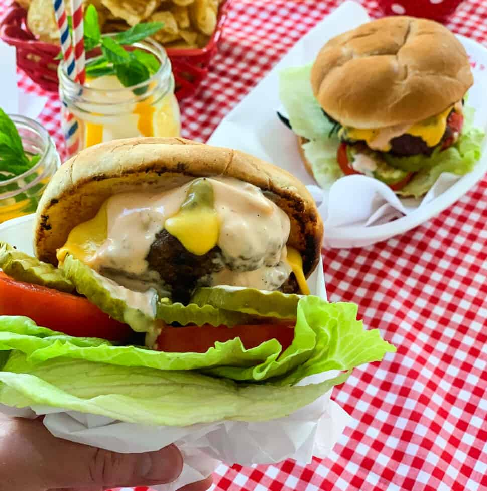 A person holding a messy grilled burger topped with melted cheese, burger sauce, lettuce, tomato, and pickles.