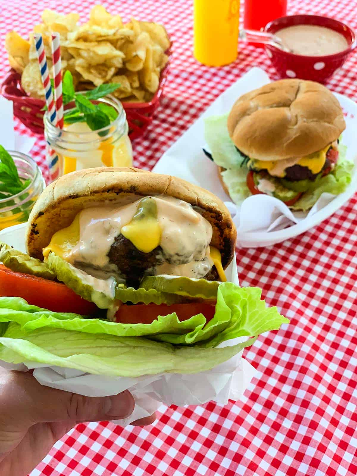 A lady holding a messy grilled cheeseburger wrapped in paper with baskets of burgers in the background.