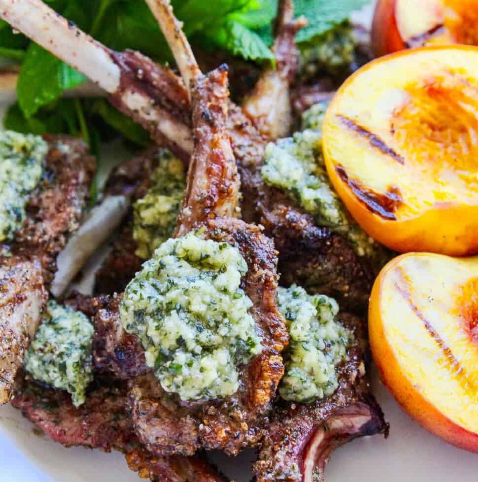A white platter filled with grilled lamb chops topped with mint pesto and grilled peaches.