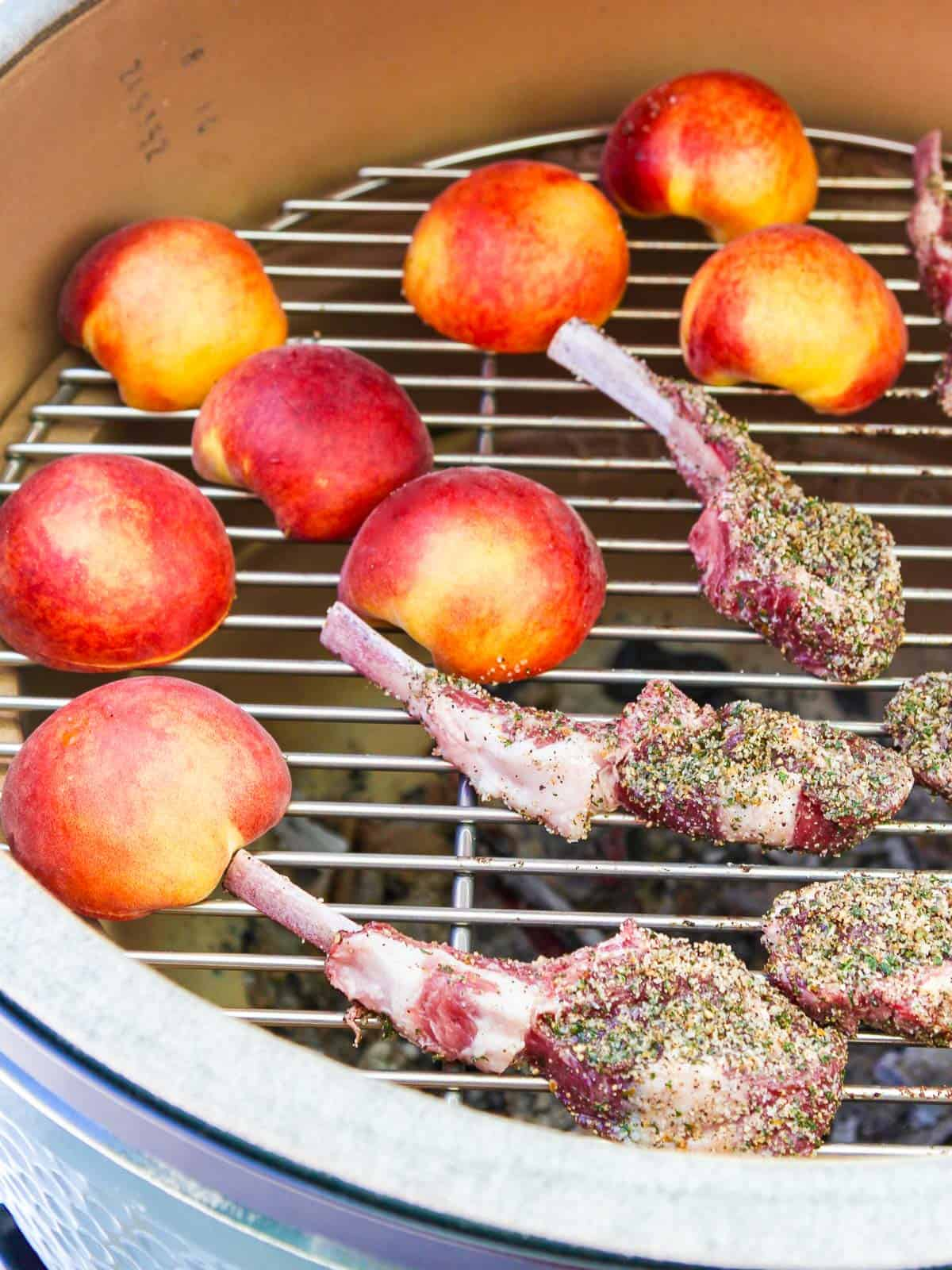 A charcoal grill with lamb chops and peaches grilling over hot coals.