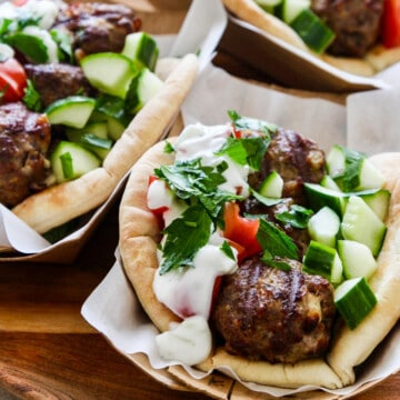 Greek gyros on parchment paper topped with lamb meatballs cucumber and tomatoes.