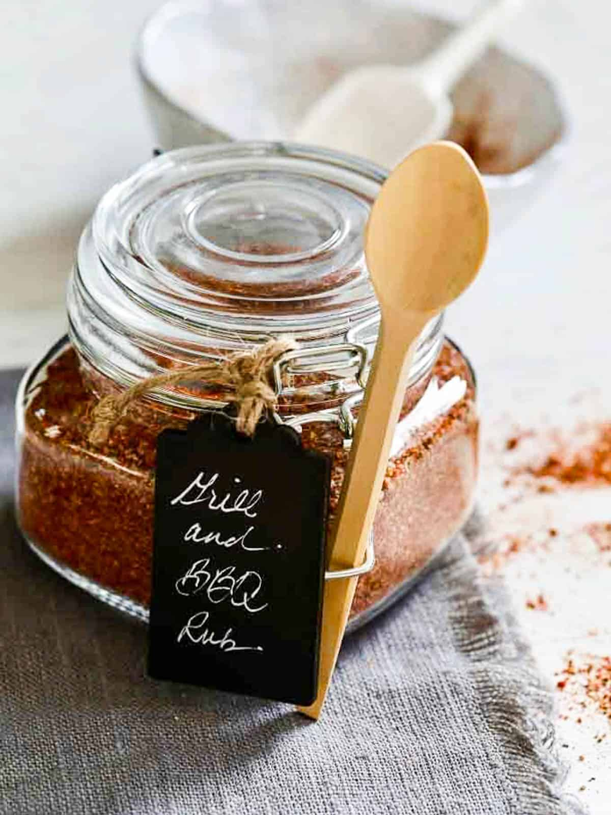 A small glass clamp jar filled with Grill and BBQ rub mix and a black tag and wood spoon wrapped as a gift.