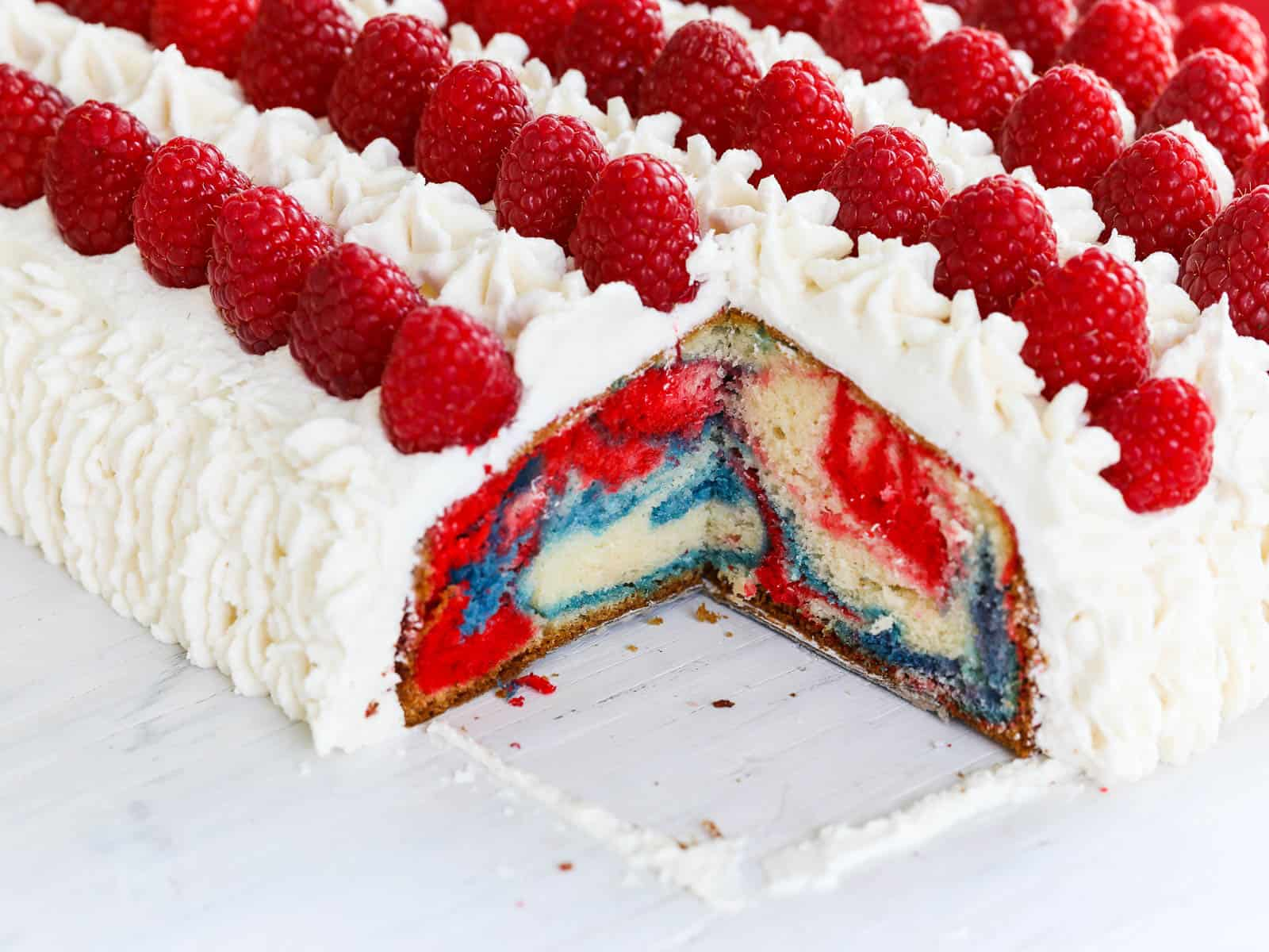 Looking at the corner of a sheet cake sliced out, with red white and blue marbled cake.