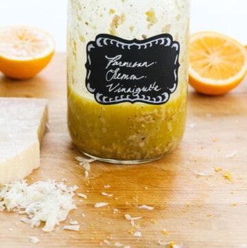 A mason jar with lemon vinaigrette inside on a messy cutting board.