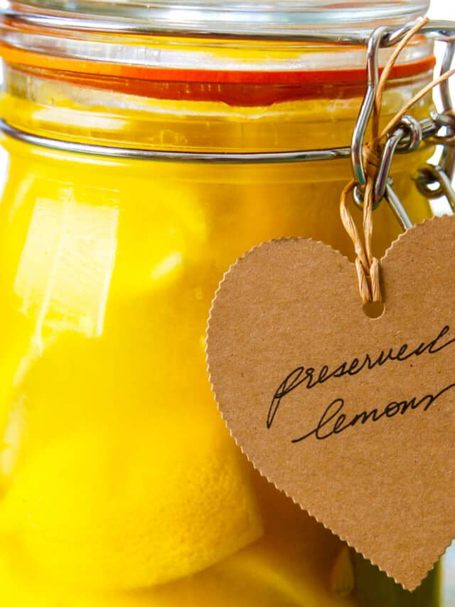 A large clamp jar of Preserved Lemons with a brown craft paper tag that says Preserved Lemons.