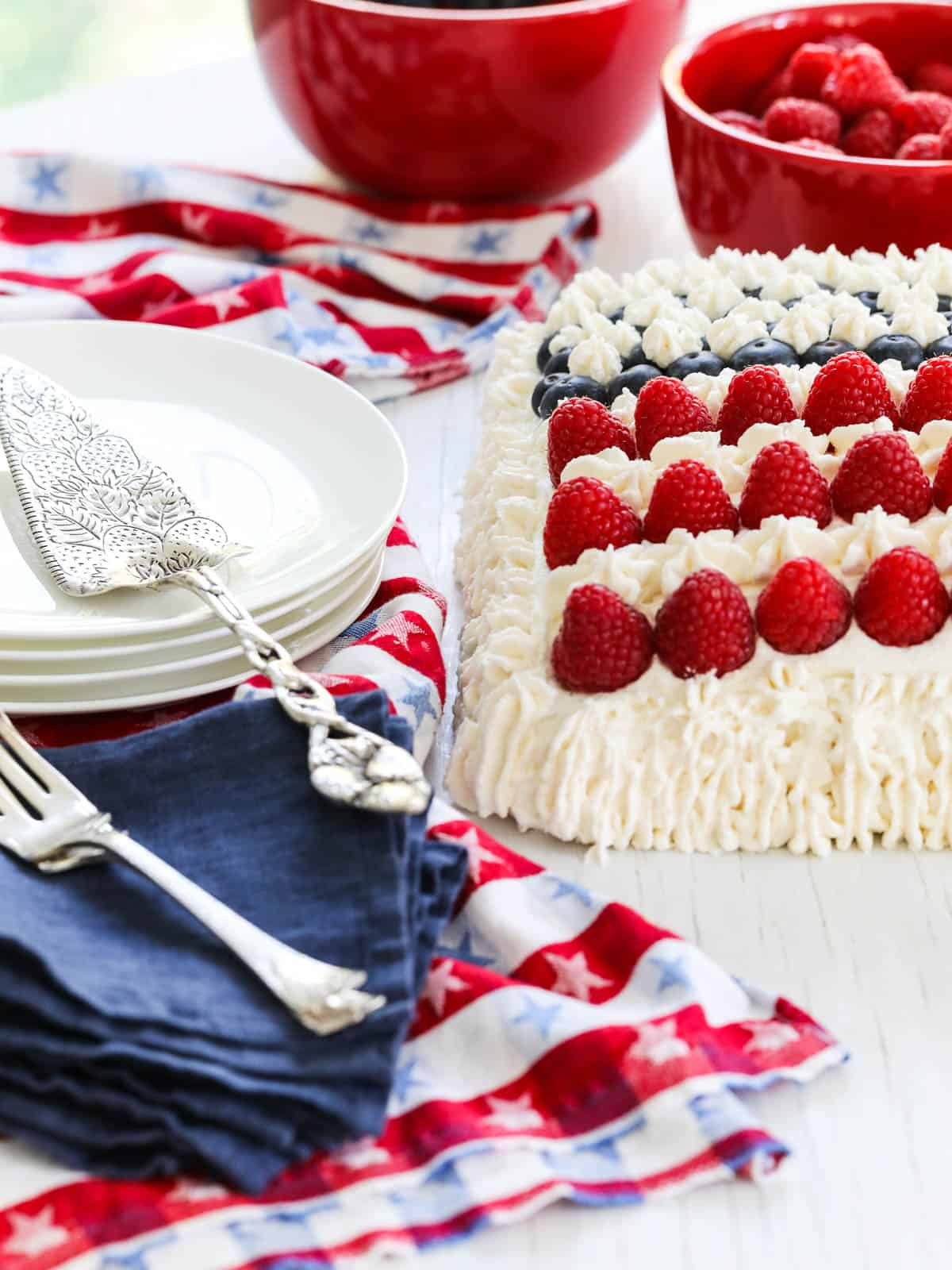 Close up of the corner on a Flag Cake decorated with white frosting, raspberries, and blueberries.