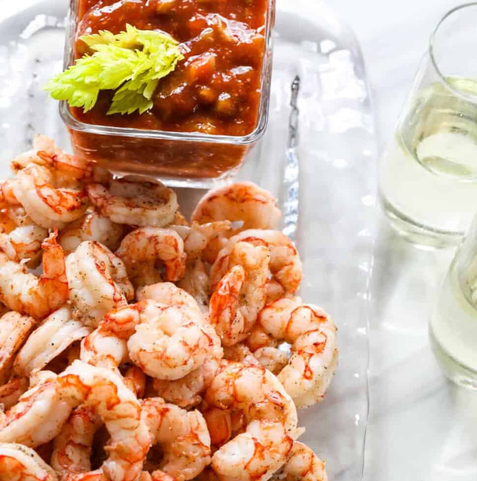 A clear glass plate with shrimp cocktail, cocktail sauce, and two glasses of champagne.