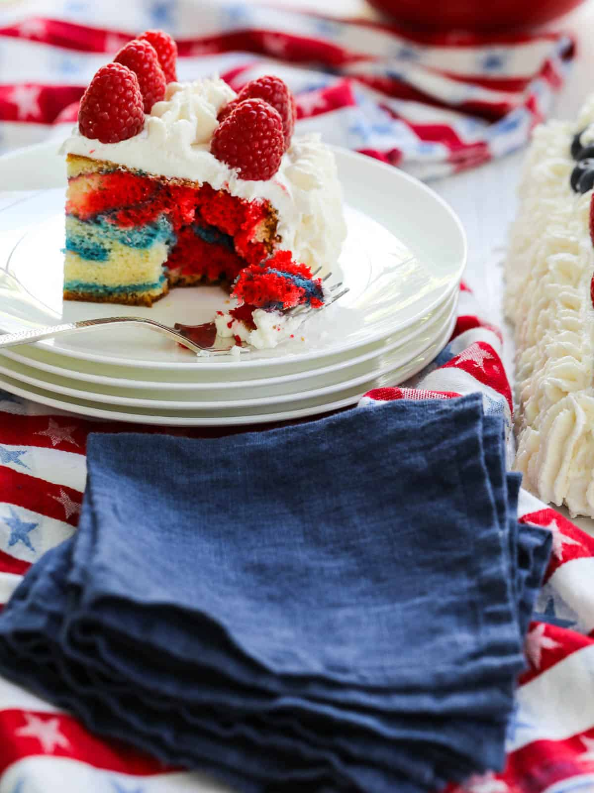 One slice of red white and blue marbled cake decorated with white frosting and raspberries.