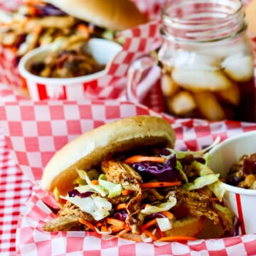 Red white check paper lined basked holding a pulled pork sandwich topped with coleslaw.