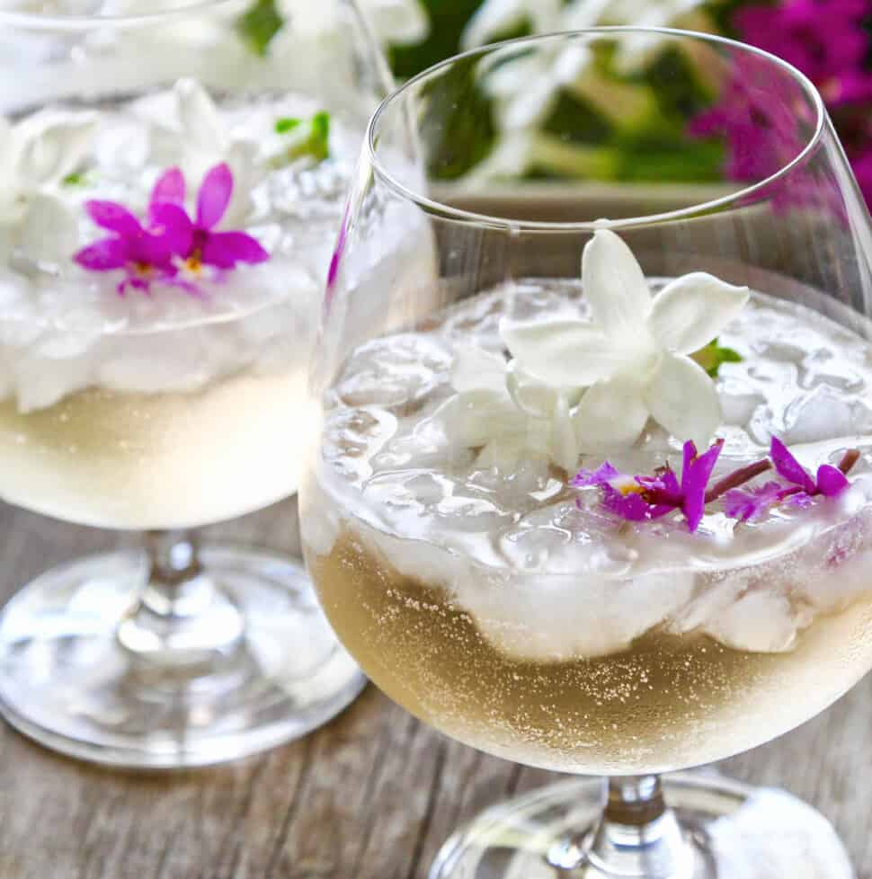 Two glasses filled with St Germain cocktails garnished with tiny purple orchids and white jasmine flowers.