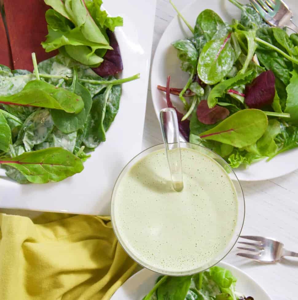 A small glass bowl with green goddess dressing and white plates of salad on a table.