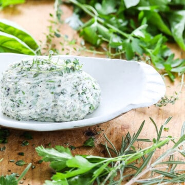 A white dish filled with herb butter and herbs on a vintage cutting board.