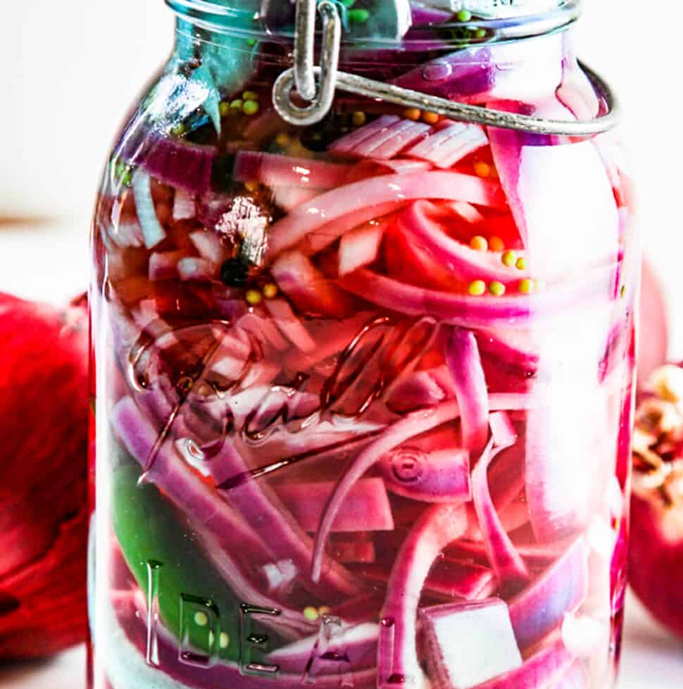 A tall aqua blue vintage glass clamp jar with red onions and green chile and garlic in the jar.