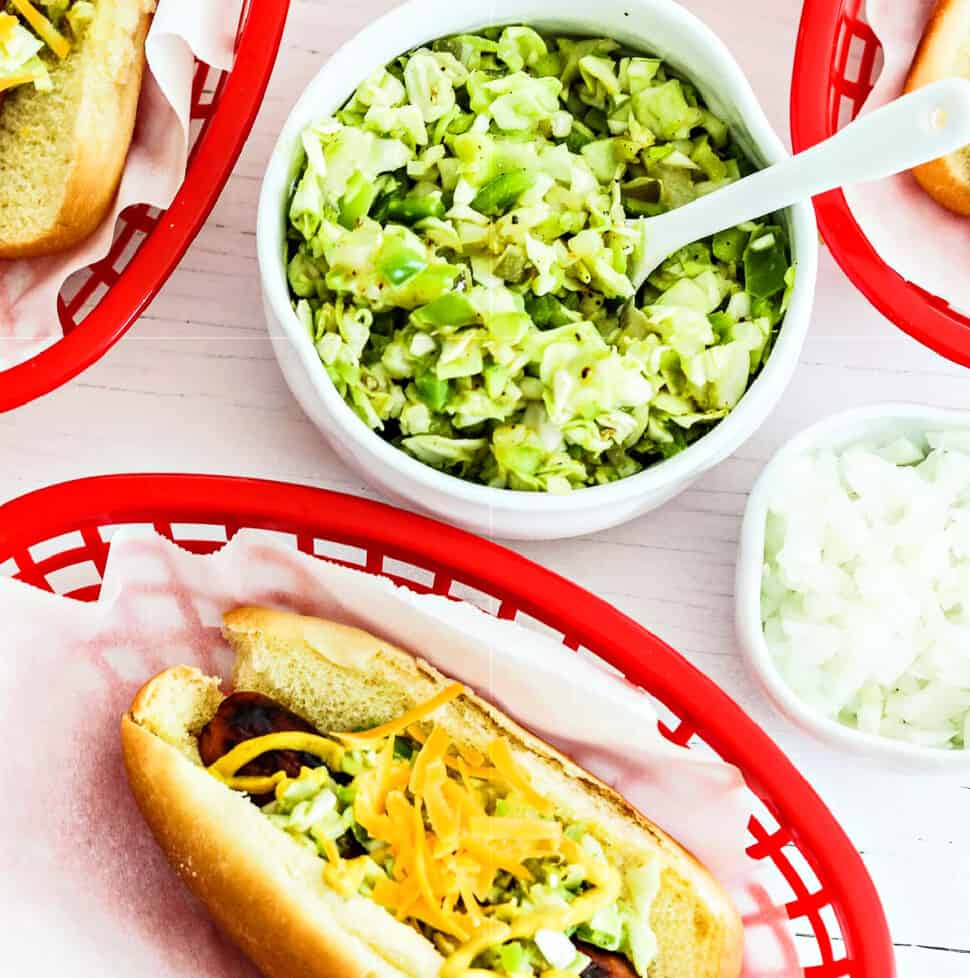 A small white bowl with relish in to top hot dogs in paper lined baskets.