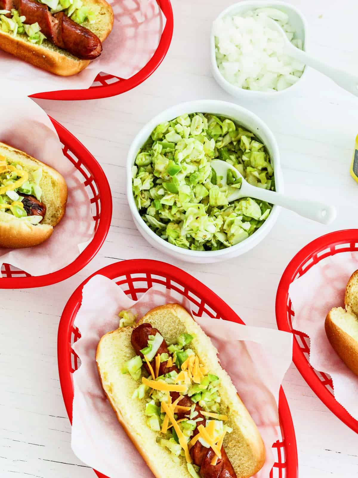 Red food baskets filled with hot dogs and toppings at a cookout party.