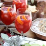 Three glasses of Aperol Spritz on a table with appetizers at a Fall party.