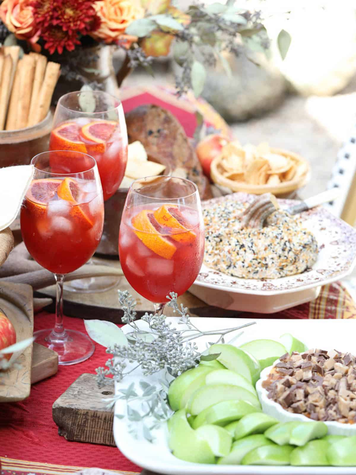 A Fall table filled with appetizers and Aperol Spritz drinks at an outdoor party.