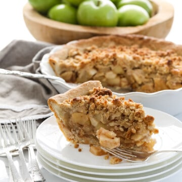 A white pie dish with a slice of apple crumble pie, also known as a dutch apple pie with a crumbled topping and green apples in the background in a wood bowl.