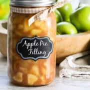A large jar filled with apple pie filling with a lid and bow.