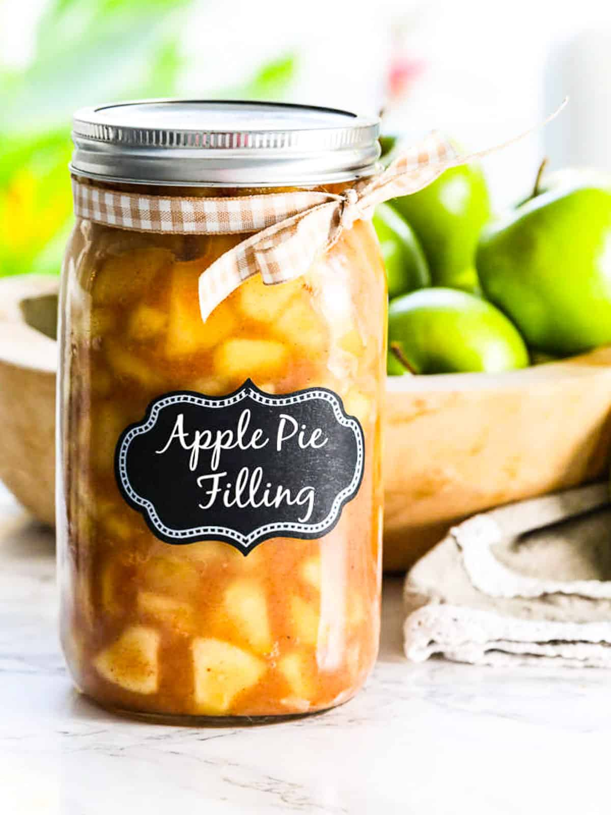 A large glass jar filled with apple pie filling and wood bowl of green apples.