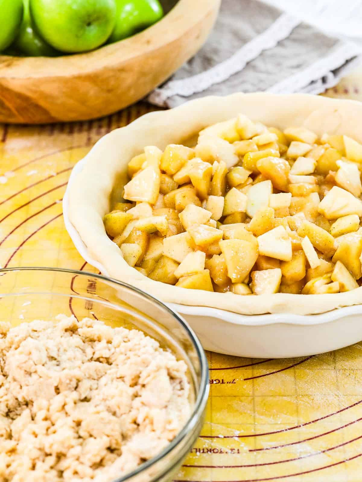 A white pie dish with pie dough filled with apple pie filling ready to bake.