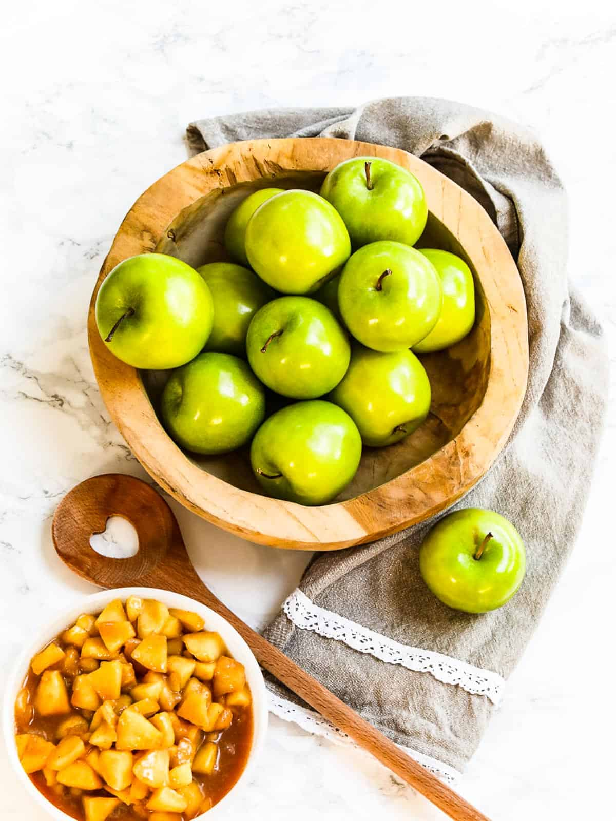 A wood bowl filled with green apples a towel, and bowl of cooked apple pie filling.