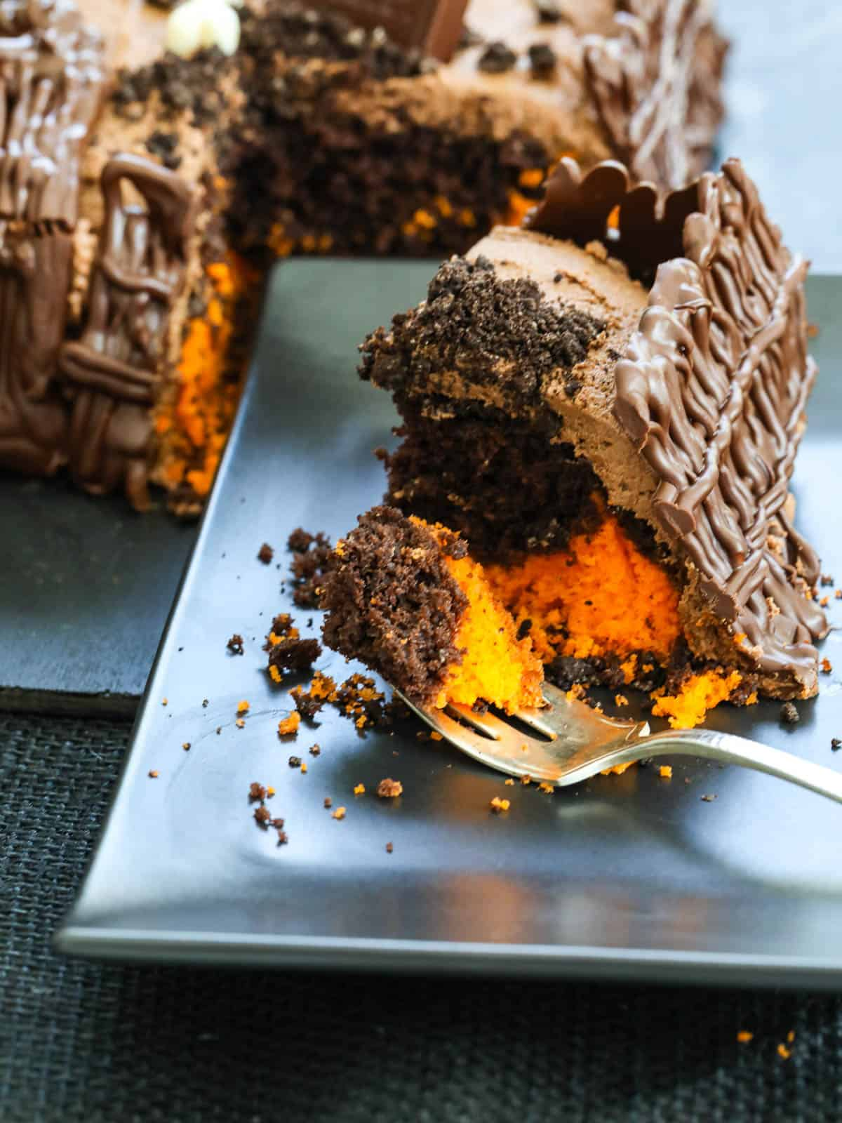 A slice of orange and chocolate Halloween cake on a black plate with a fork.