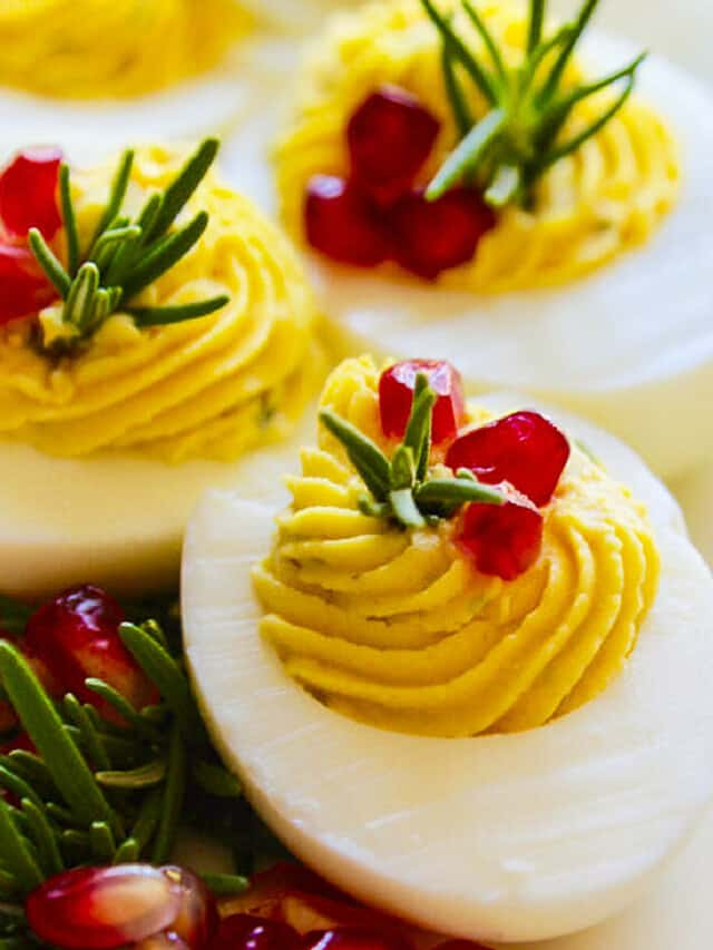 White platter with Christmas Deviled Eggs garnished with rosemary and pomegranate seeds.
