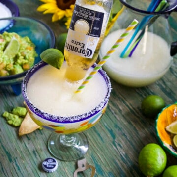A Cinco de Mayo party with frozen margaritas, guacamole, and chips on a green table.
