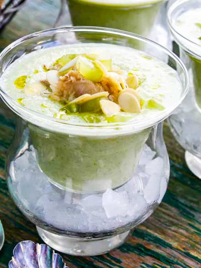 Chilled cucumber soup topped with crab meat and grape garnish served in bowls over ice.