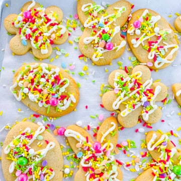 Easter cookies with sprinkles and icing on parchment paper lined cookie tray.