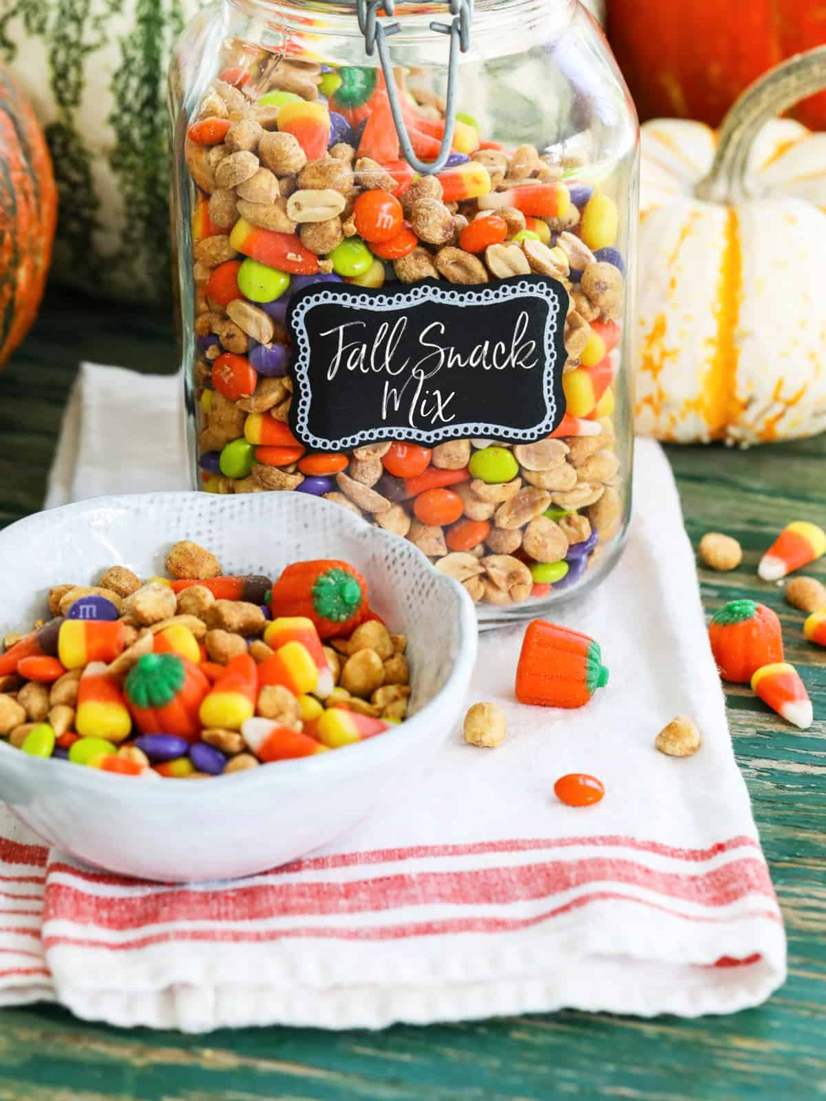 A large glass jar filled with a Fall Snack Mix with candy corn and M&Ms with a small bowl of it nearby.