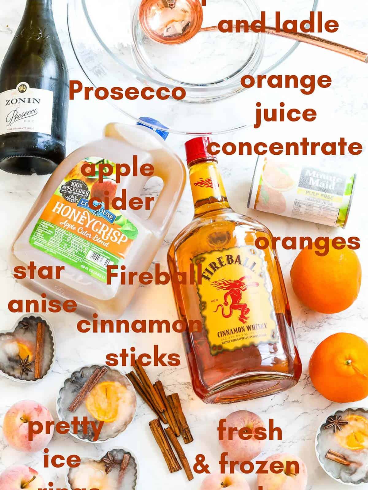 All the ingredients to make Fireball Thanksgiving punch labeled on a table including prosecco and apple cider.