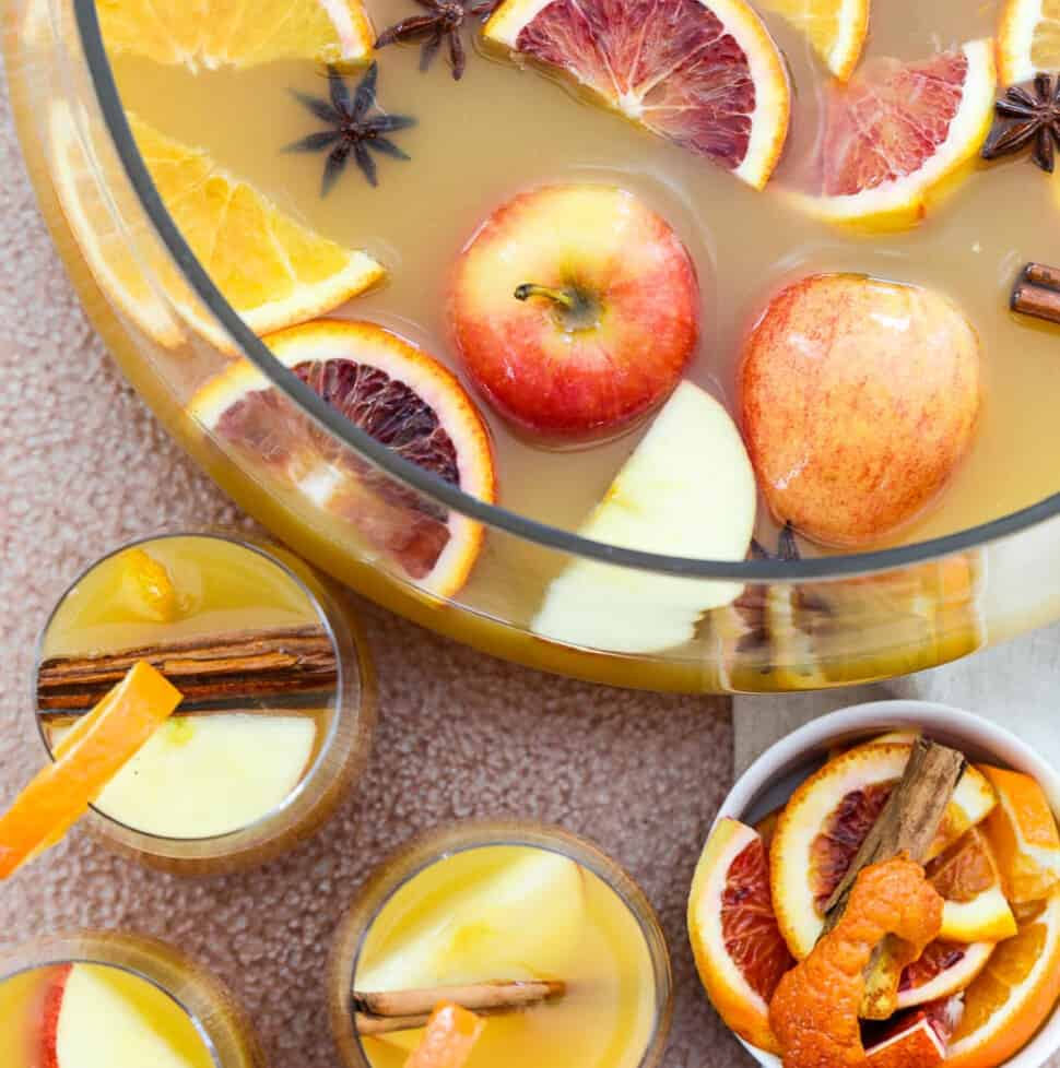 A large glass punch bowl filled with Fall and Thanksgiving punch with apples and oranges floating on top.