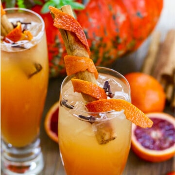 Fireball Whisky Cocktails with cinnamon sticks wrapped in orange peel for garnish.