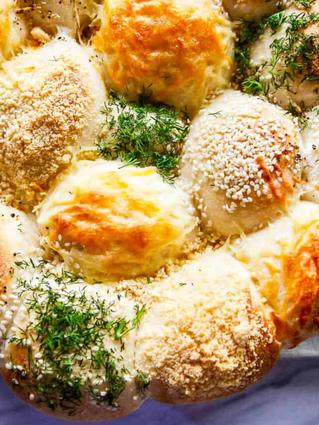 A close up of baked Frozen Dinner Rolls topped with cheeses, herbs, and seasonings.