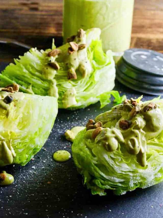 Wedge salad with avocado dressing drizzled on top with pistachios on a black slate board.