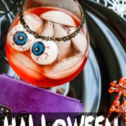 A large glass with black sugar on the rim, ice, and large plastic eyeballs in these Halloween Cocktails.