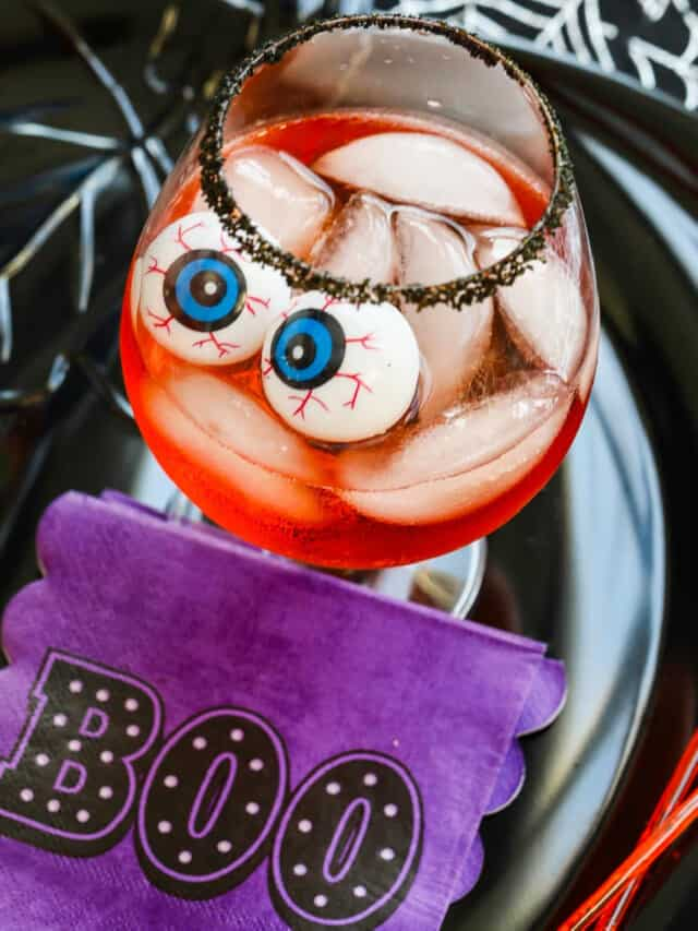 A large cocktail glass with black sugar rim, ice, Aperol Cocktails, and eyeballs for Halloween.