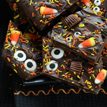 A pile of Halloween bark on a dark black platter decorated with candy and sprinkles.