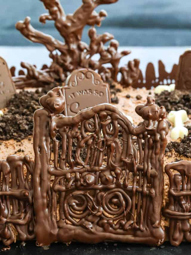 A chocolate Halloween Cake with gate, fence, tree and tombstones.