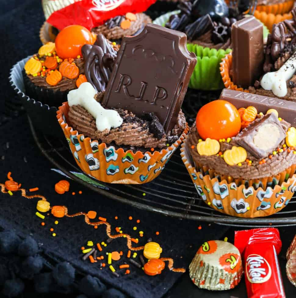 Close up of decorated Halloween cupcakes with chocolate frosting, candy, sprinkles on a vintage cooling rack.